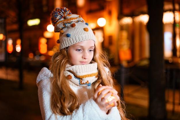 겨울 거리에서 저녁에 그녀의 손에 화환을 들고 아름다운 소녀
