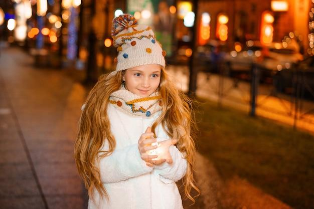 겨울에 거리에서 저녁에 그녀의 손에 화환을 들고 아름다운 소녀