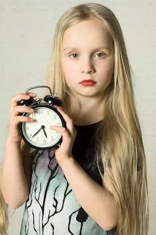 Красивая девушка держит будильник
