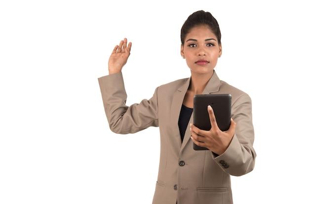 Красивая девушка держит и представляет что-то в руке со смартфоном или планшетом