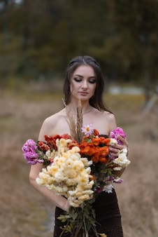 Beautiful girl holding a bouquet of flowers in the woods
