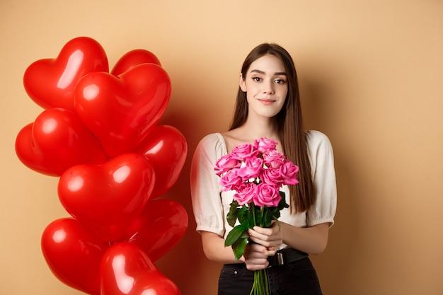 ピンクのバラの花束を持って、ロマンチックなデートに立っているカメラに微笑んでいる美しい少女...
