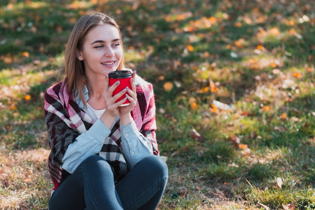 Beautiful girl holding a coffee cup and looking away