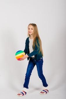 白、スタジオで隔離の色の明るいボールを保持している美しい少女