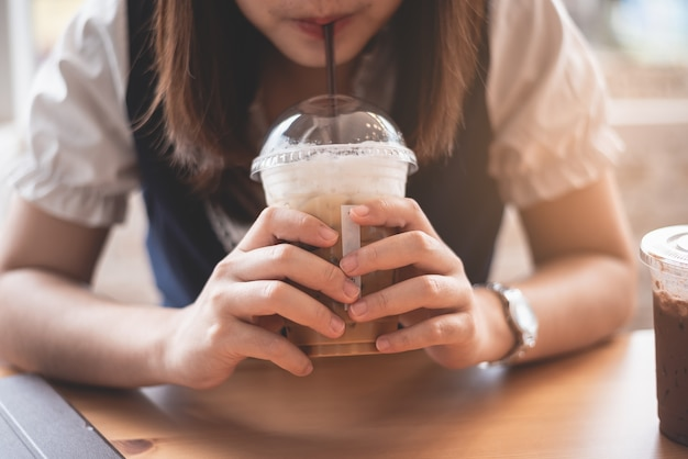 Beautiful girl holding a cup of ice coffee in the cafe
