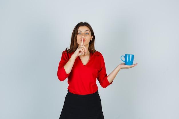 Bella ragazza che tiene una tazza, che mostra gesto di silenzio in camicetta rossa, gonna nera e sembra seria, vista frontale.