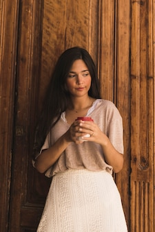 Beautiful girl holding disposable coffee cup standing against wooden door