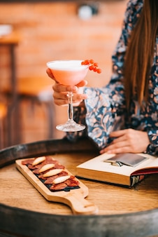Beautiful girl holding an exquisite creamy cocktail in a special glass at the bar sits on a table in the form of a wooden barrel