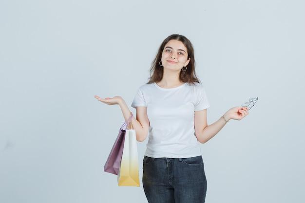 Tシャツ、ジーンズ、親切に見えるギフトバッグを保持している美しい少女。正面図。