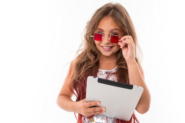 Beautiful girl holding light grey tablet touches square red sunglasses on her face isolated
