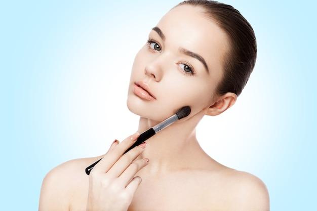 Beautiful girl holding makeup brush foundation on white background