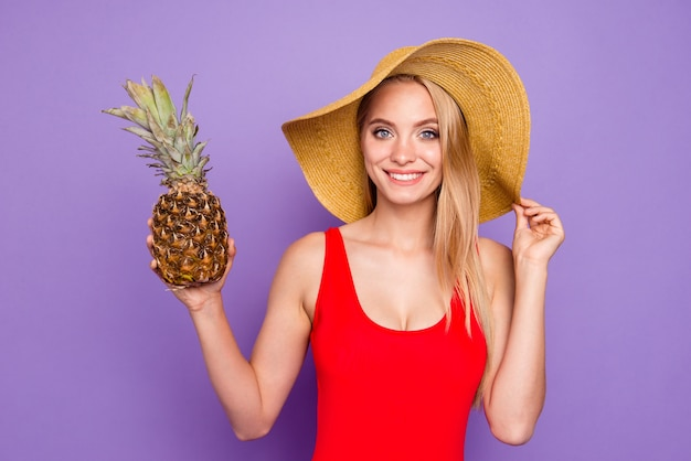 Beautiful girl holding pineapple cocktail in her hand