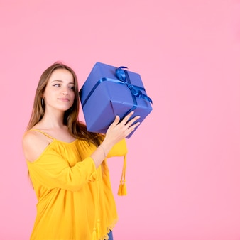 Beautiful girl holding wrapped gift box against pink background