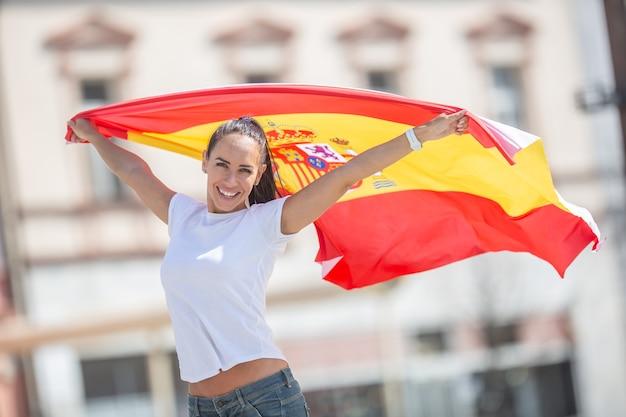 아름다운 소녀는 뒤에서 손에 스페인 국기를 들고 거리에서 응원합니다.