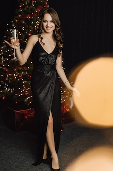 Beautiful girl holds a glass with champagne and smiles standing in front of a christmas tree