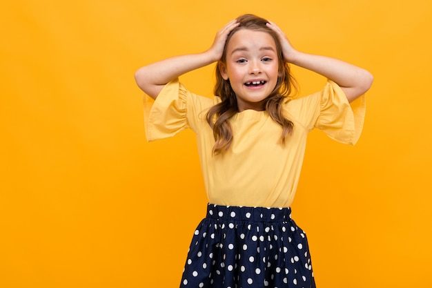 Beautiful girl holds her head with hands on a  of an orange wall, emotional portrait