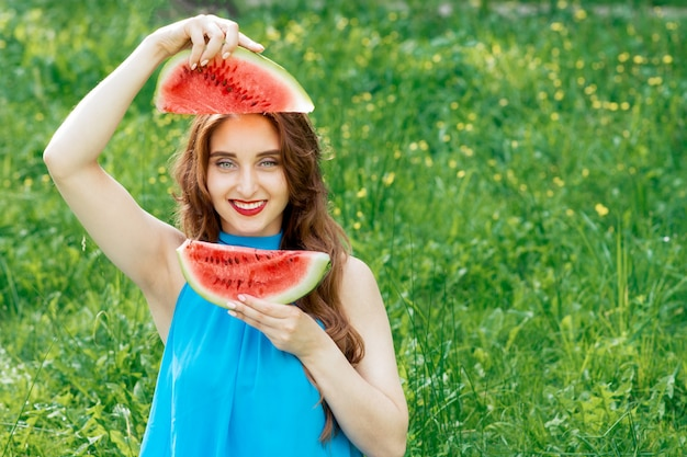 Beautiful girl holds two slices of watermelon