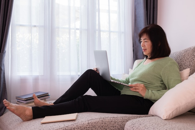 Beautiful girl at home using laptop on the couch, elderly asian woman.