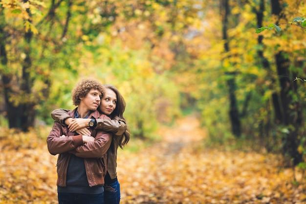 秋の公園で巻き毛の口ひげを生やした男を抱き締める美しい少女