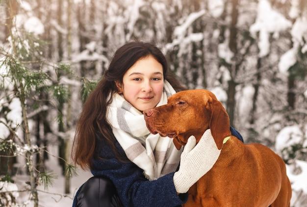 美しい少女は冬の森から散歩で彼女の犬を抱きしめます