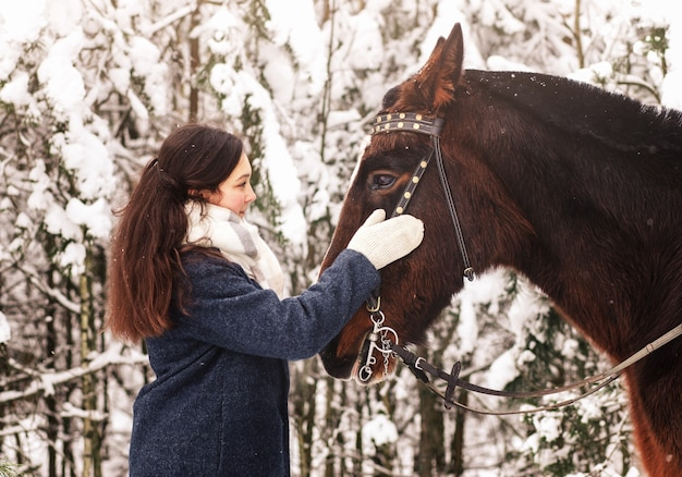 A beautiful girl hugs a horse in winter in nature. walking in the woods