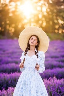 大きな帽子とラベンダーの背景に正装の美しい少女。彼女の髪に三つ編みの若いモデル。太陽の下での夏の写真。