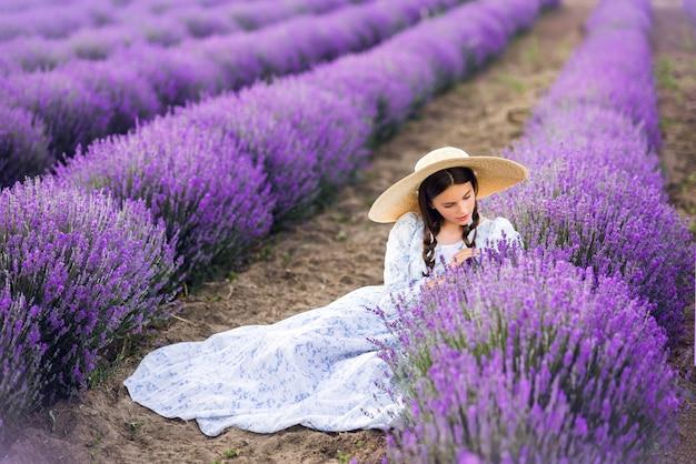 Красивая девушка в большой шляпе и длинном платье собирает лаванду. фото лета.