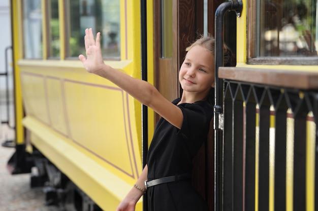 黒のドレスを着た美しい少女が路面電車から降りて手を振る
