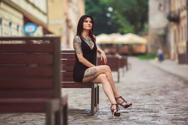 Красивая девушка в черном платье сидит на скамейке, покрытой татуировками