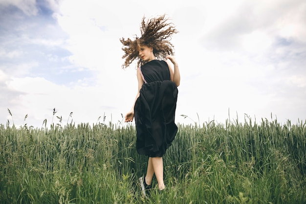 緑の野原に立って髪を羽ばたく黒いドレスの美しい少女