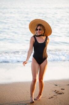 일몰 햇빛에 바다에서 모래 해변에 검은 수영복과 모자에 아름 다운 소녀