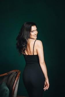 黒のタイトフィットのドレスとハイヒールの美しい少女。黒の長いウェーブのかかった髪。東部の外観。
