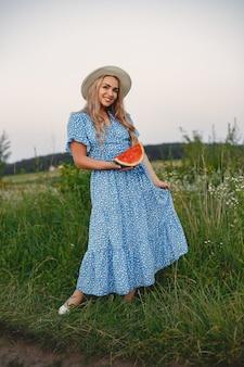 青いドレスと帽子で美しい少女。夏の畑の女性。スイカを持つ少女。