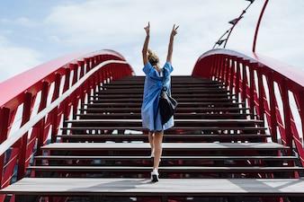 Beautiful girl in a blue dress posing on the bridge