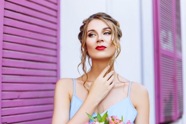 Красивая девушка в голубом платье позирует на улице возле кафе с розовыми окнами