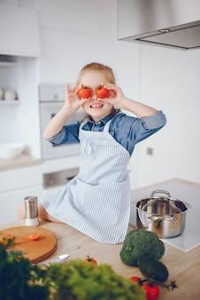 青いシャツとエプロンの美しい少女は、自宅で新鮮な野菜サラダを準備しています
