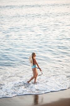 일몰 햇빛에 바다에서 모래 해변에 파란색 수영복과 모자에 아름 다운 소녀