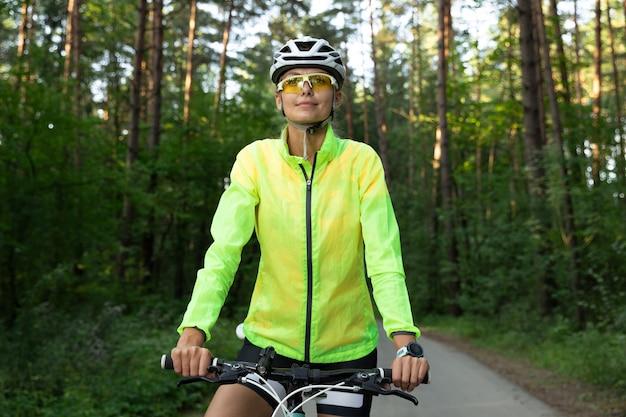 Красивая девушка в ярко-зеленой ветровке, шортах, очках и шлеме отдыхает после езды на велосипеде в лесу