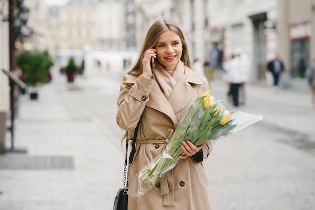 갈색 코트에서 아름 다운 소녀입니다. 봄 도시에있는 여자. 꽃의 부케와 레이디