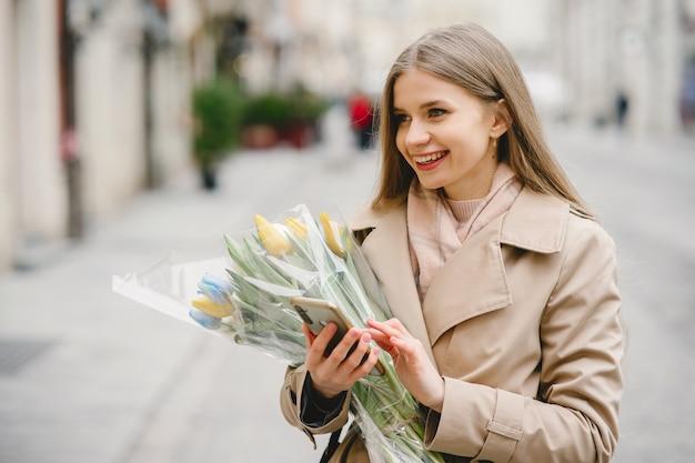 茶色のコートを着た美しい少女。春の街の女性。花の花束を持つ女性