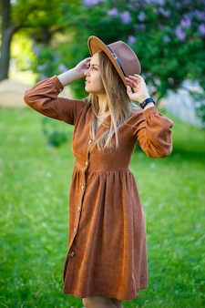 Красивая девушка в коричневой шляпе, стоя возле куста сирени. молодая женщина возле цветущего дерева.