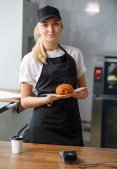 クロワッサンを保持しているカフェやパン屋の美しい少女