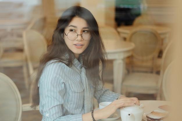 Красивая девушка в кафе пьет чай