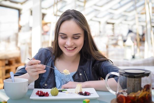 Красивая девушка в кафе сидит за столом и ест чизкейк Premium Фотографии