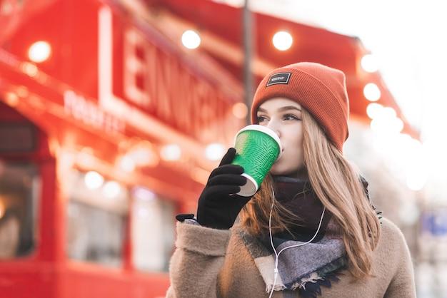 봄 시즌에 거리에서 컵 커피를 마시는 모자에 아름다운 소녀