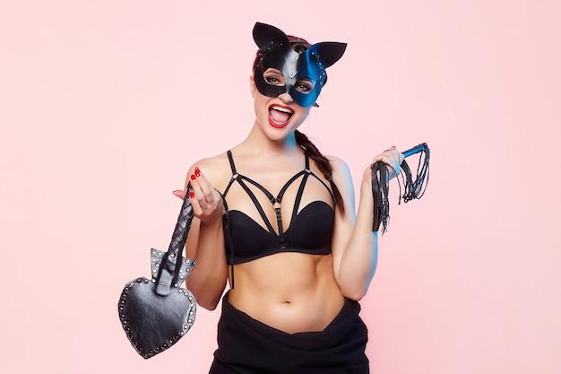 Красивая девушка в маске кошки. игриво позирует