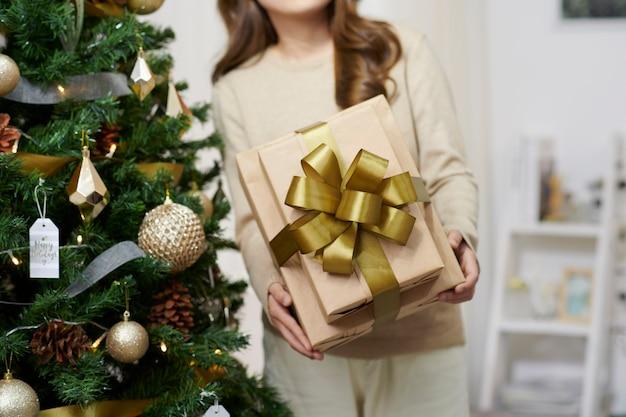 飾られた部屋の美しい少女。クリスマスツリーの近くの女性。セーターの女性