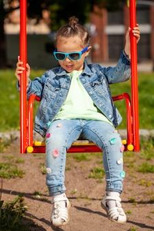 Красивая девушка в джинсовом костюме и солнцезащитных очках качается на качелях