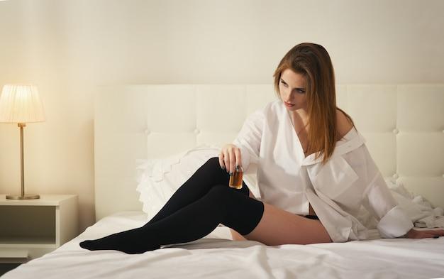 白い寝室のうつ病の美しい少女はアルコールを飲む