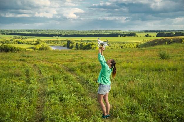 Красивая девушка в поле запускает беспилотник в небо